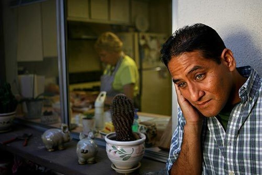 """Luis Garcia, a successful physician from Peru, still needs to pass the U.S. licensing exams. While studying, he takes care of cats, dogs and elderly people in Southern California. Garcia is shown at the residence of Dusha Cvjetkovic (in the background cooking), whose home and cat he's cared for intermittently over the last two years. Cvjetkovic, originally from Croatia, says that although she has paid Garcia to help her with her garden, her cat and her home, she would be embarrassed to ask him to do dirtier jobs. """"In my country a doctor is someone to be very respected,"""" she said."""
