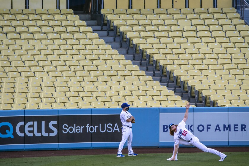 Dodgers starting pitcher Dustin May stretches in front of empty seats before the Dodgers' season opener.