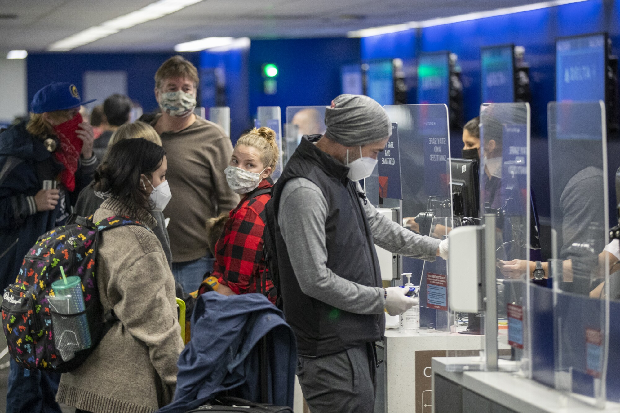 People wearing masks check in at LAX as Thanksgiving holiday travel gets underway.