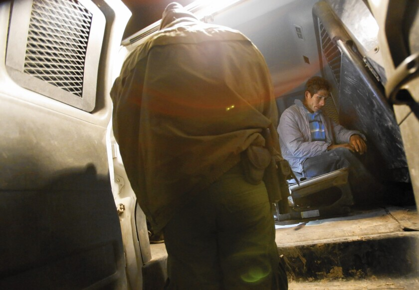 Border Patrol agents apprehend immigrants, most of them from Central America, near McAllen, Texas. The number of people caught at the border and deported fell 9% in the last year.