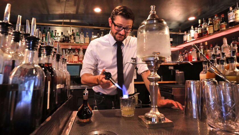 "Bar manager Cory Volkening uses a torch to heat a sugar cube as he uses an absinthe fountain, at right, to create a powerful absinthe cocktail at The Charles Kenneth ""speakeasy"" bar. It's in the basement of the historic building that houses the Land & Wat"