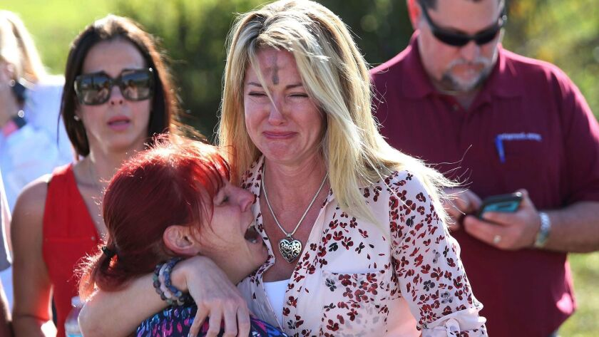 Parents wait for news after a reports of a shooting at Marjory Stoneman Douglas High School in Parkland, Fla., on Feb. 14.