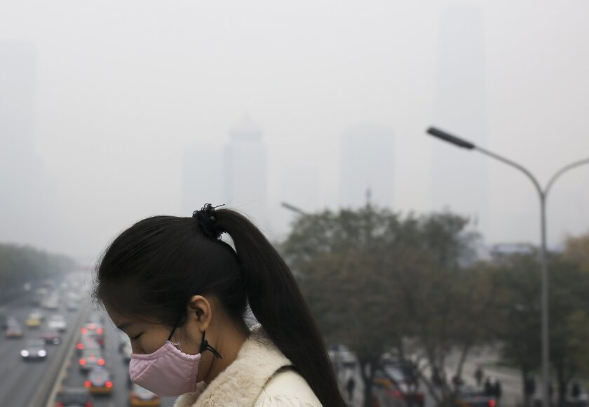 A woman wears a mask to protect herself from pollutants during a hazy day in Beijing on Nov. 19.