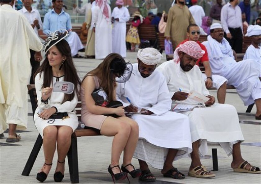 a woman in western dress helps an Arab to go through the race catalogue, during the Dubai World Cup horse race, Saturday, March 31, 2012, in Dubai, United Arab Emirates. (AP Photo/Kamran Jebreili)