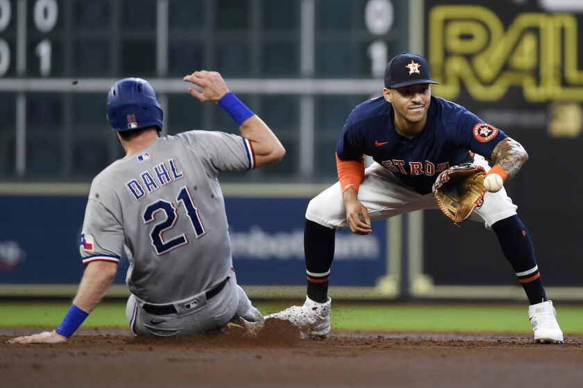 Houston Astros shortstop Carlos Correa, right, puts out Texas Rangers' David Dahl during a fielder's choice during the second inning of a baseball game, Sunday, July 25, 2021, in Houston. Brock Holt was safe at first. (AP Photo/Eric Christian Smith)