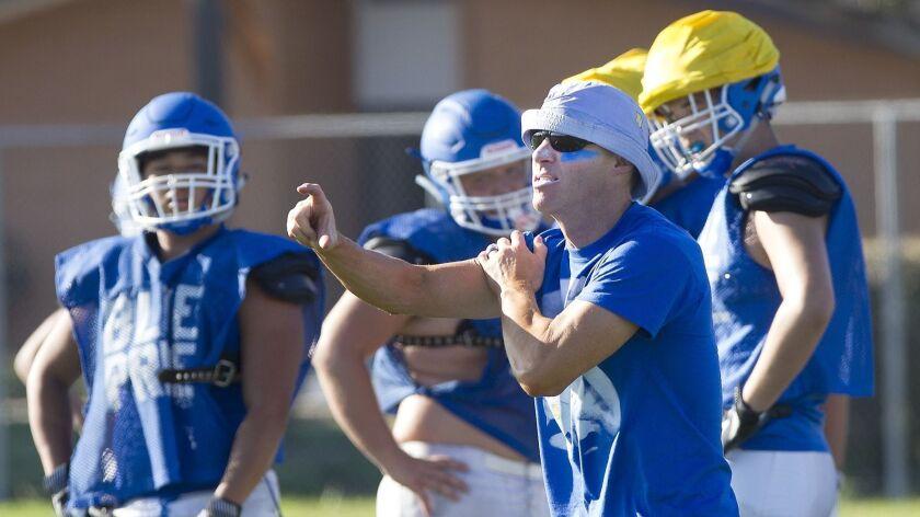 Fountain Valley football coach Jimmy Nolan runs players through drills during recent practice.