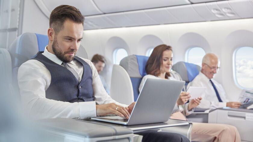 Businessman working at laptop on airplane