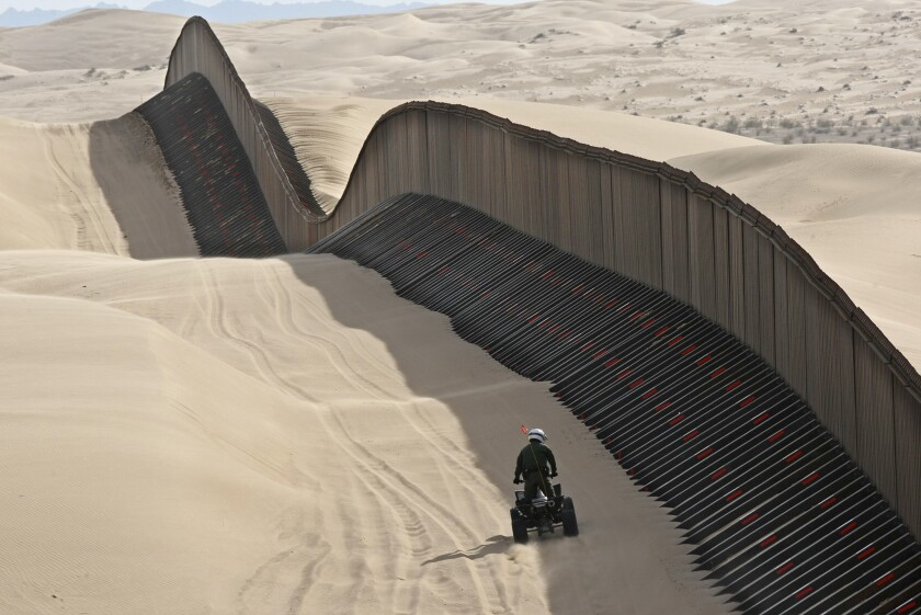 """MARCH 4, 2009. IMPERIAL SAND DUNES, CA. A U.S. Border Patrol agent rides an ATV along the """"floatin"""