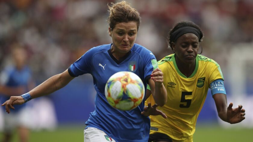 Italy's Cristiana Girelli, left, fights for the ball with Jamaica's Konya Plummer during the Women's
