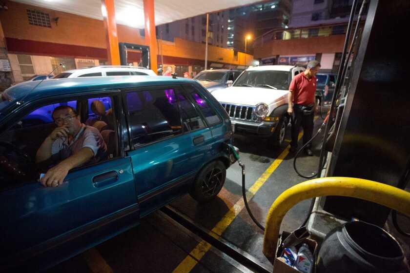 Un conductor carga gasolina en su auto en Caracas, Venezuela. El presidente venezolano Nicolás Maduro anunció el miércoles un incremento de entre 1.328 y 6.566% de los precios de la gasolina, una de las más baratas del mundo y que se mantuvo congelado por más de 17 años, así como la creación de un nuevo sistema de control de cambios que tendrá dos bandas, como parte de una serie de medidas para hacer frente a la severa crisis económica que vive Venezuela y que se prevé empeore por la caída de los precios del petróleo. (AP Foto/Fernando Llano)
