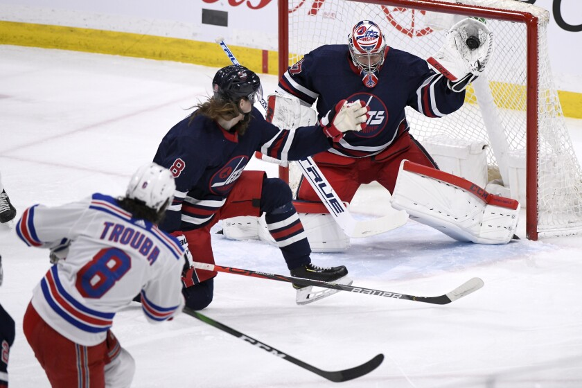 Winnipeg Jets goaltender Connor Hellebuyck (37) makes a save on a shot from New York Rangers' Jacob Trouba (8) during first period NHL hockey action in Winnipeg, Manitoba on Tuesday Feb. 11, 2020. (Fred Greenslade/The Canadian Press via AP)