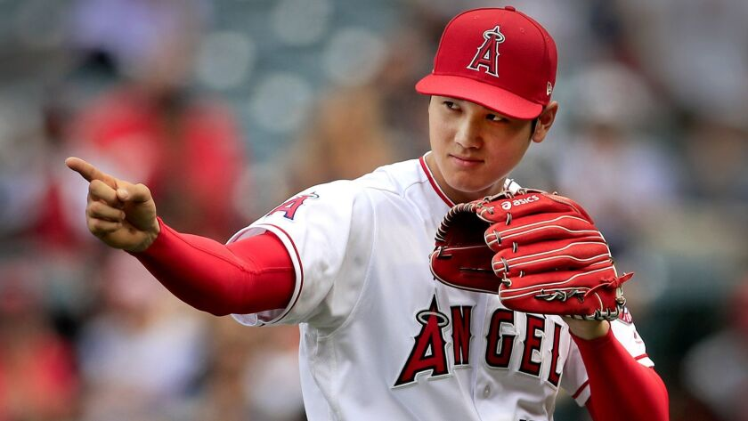 ANAHEIM, CALIF. -- SUNDAY, MAY 20, 2018: Angels starting pitcher Shohei Ohtani points to a teammate