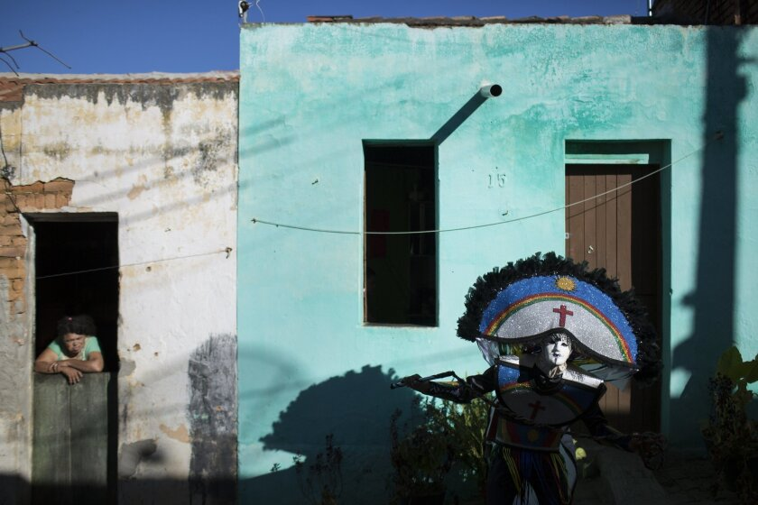 "In this Monday, Feb. 8, 2016 photo, a resident watches a ""Careta"" parade through the streets of Triunfo, Brazil. The traditional festivity dates back almost a century. Residents say it was created in this small town by two men who weren't allowed to take part in a folk celebration because they were"