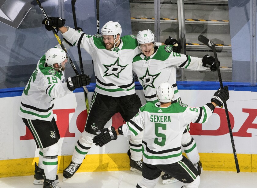 Dallas Stars' Blake Comeau (15), Jamie Oleksiak (2), Joel Kiviranta (25) and Andrej Sekera (5) celebrate the winning goal against the Colorado Avalanche during overtime of an NHL Western Conference Stanley Cup playoff game in Edmonton, Alberta, Friday, Sept. 4, 2020. (Jason Franson/The Canadian Press via AP)