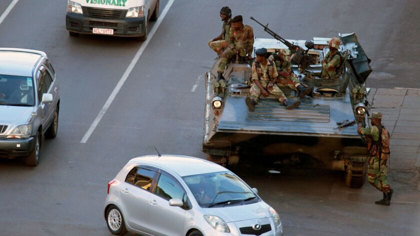 Soldier man their position with a military vehicle outside the office of President Robert Mugabe, in