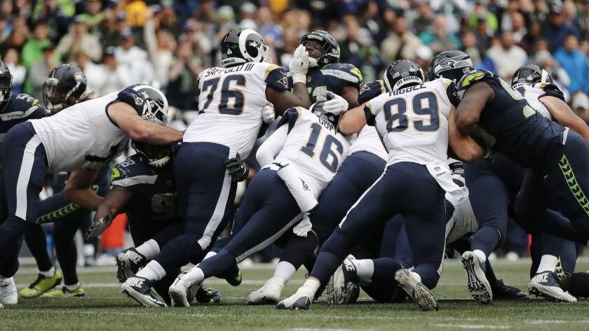 SEATTLE, WA - OCTOBER 7, 2018: Los Angeles Rams offensive line surrounds quarterback Jared Goff (16