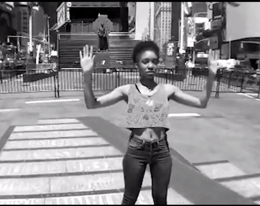 """Jes Washington stands in the """"hands up, don't shoot"""" pose in \""""Say Their Names: Hear Their Voices."""""""