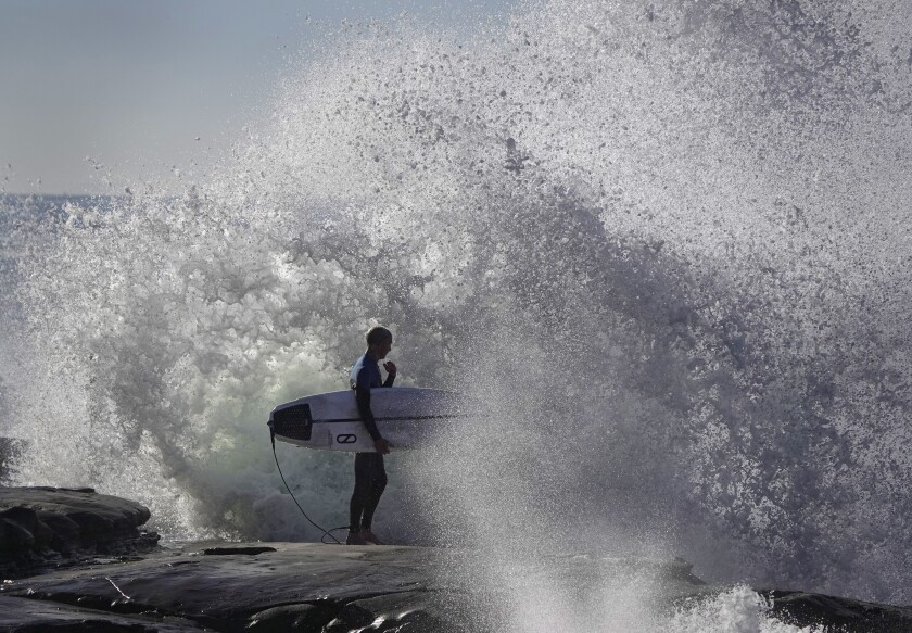 Waves crash against the rocks in La Jolla as a surfer waits to head out during a king tide.