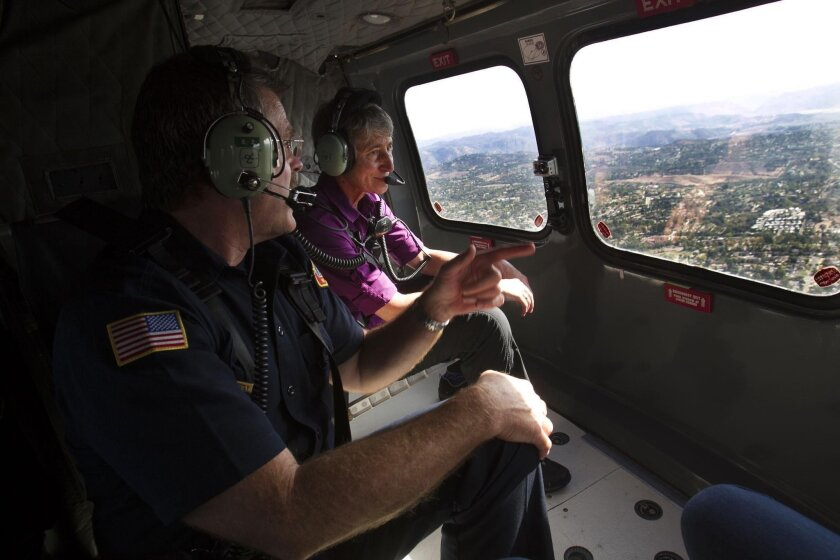 SAN DIEGO, CA-OCTOBER 14, 2015: Secretary of the Interior Sally Jewell, rear, and Rep. Scott Peters, right, not visible, toured parts of San Diego city and county with SDFD Asst. Chief Brian Fennessey, left, by helicopter and met with federal and state firefighters in Peters' effort to get wildfire counted in as a natural disaster at the Federal level.(JOHN GIBBINS / San Diego Union-Tribune)