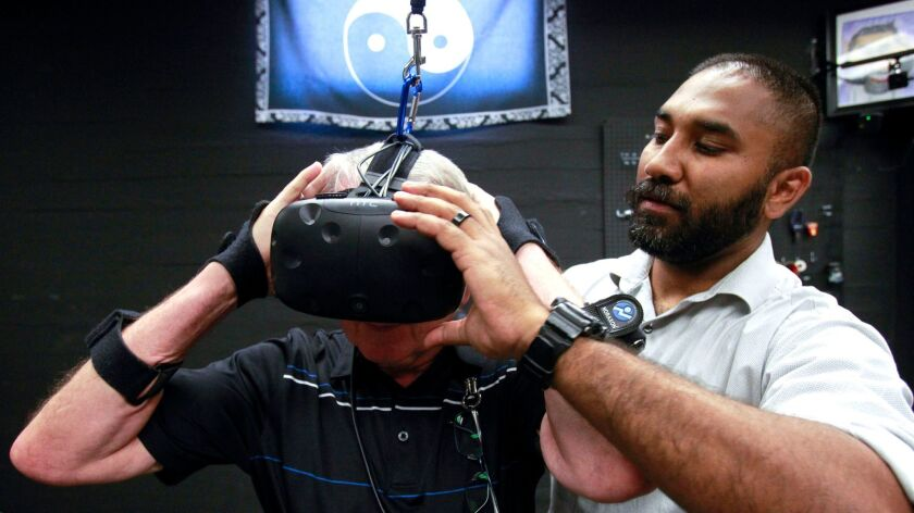 Harsimran Baweja puts a virtual reality headset on Ken Goble at San Diego State University on June 15, 2017.