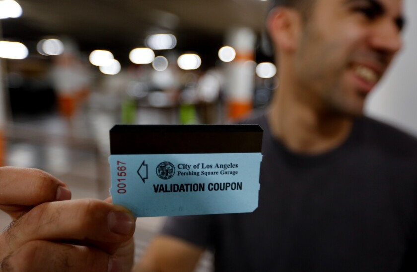 Downtown Los Angeles employee Andy Agopyan holds his ticket voucher in the Pershing Square garage. Thanks to a class-action lawsuit, parking is free in the Pershing Square underground parking garage for a limited time.