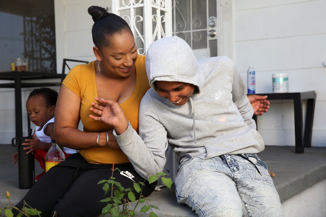 A woman plays on the porch of her South L.A. home with two of her children