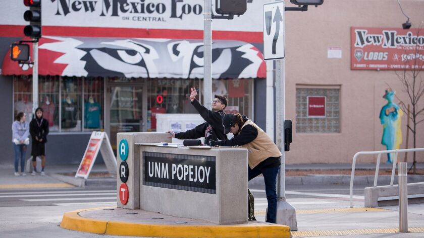 Architecture students use a non-functioning bus stop on Albuquerque's Central Avenue to sketch a building.