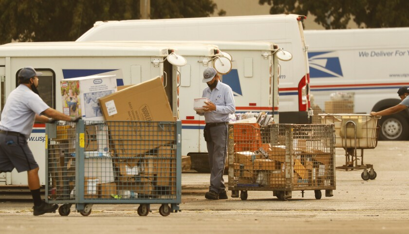 Mail carriers load letters and parcels from large carts into their trucks at a U.S. post office in Van Nuys.