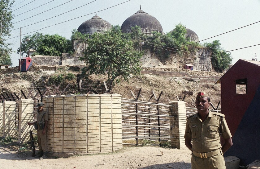 FILE - In this Oct. 29, 1990, file photo, Indian security officer guards the Babri Mosque in Ayodhya, closing off the disputed site claimed by Muslims and Hindus. India's top court is expected to pronounce its verdict on Saturday, Nov. 9, 2019, in the decades-old land title dispute between Muslims and Hindus over plans to build a Hindu temple on a site in northern India. In 1992, Hindu hard-liners demolished a 16th century mosque in Ayodhya, sparking deadly religious riots in which about 2,000 people, most of them Muslims, were killed across India. (AP Photo/Barbara Walton, File)