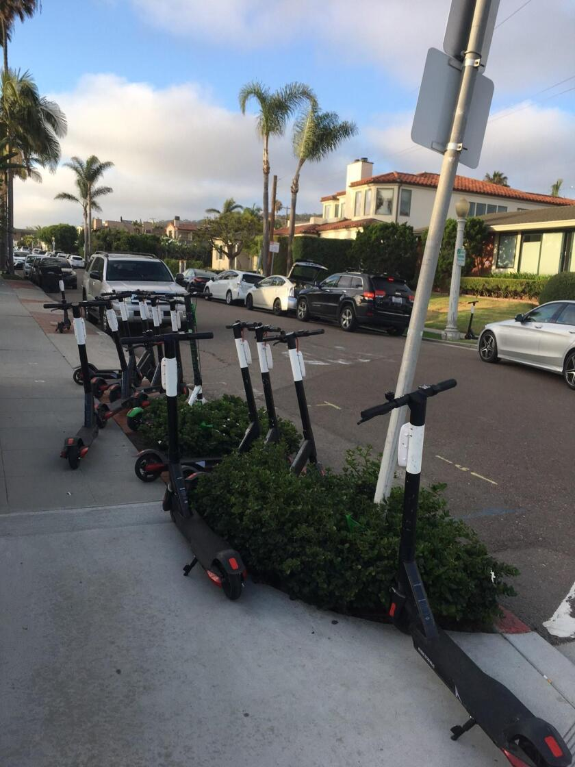WELCOME TO SCOOTERVILLE, USA: This photo was taken 7 p.m. Saturday, July 27 at the corner of Camino Del Oro and Paseo Del Ocaso in La Jolla Shores, where 13 electric scooters were sitting. People had to walk out into the street to get by them! Unbelievable to me! — Janie Emerson