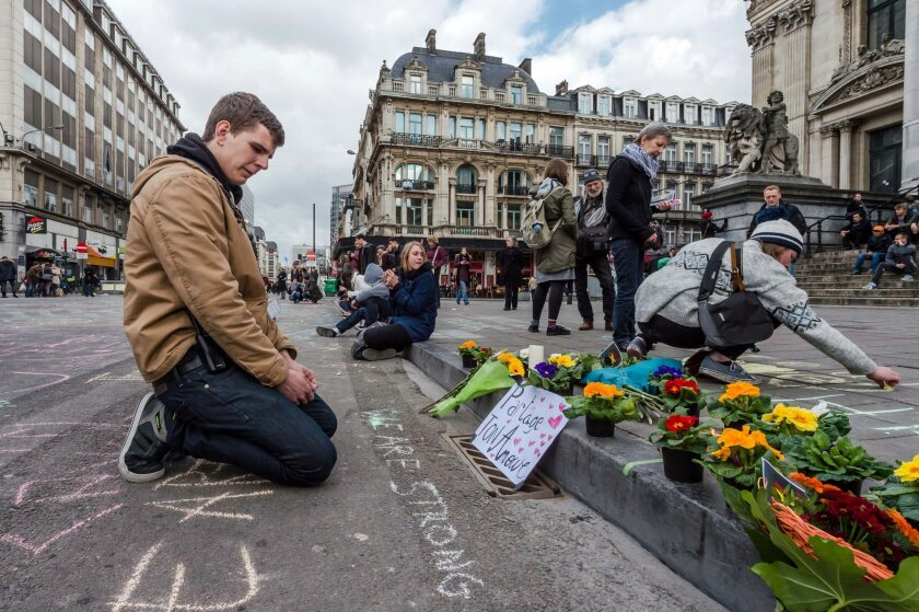 A man looks at flowers and messages outside the stock exchange in Brussels on Tuesday, March 22, 2016. Explosions, at least one likely caused by a suicide bomber, rocked the Brussels airport and subway system Tuesday, prompting a lockdown of the Belgian capital and heightened security across Europe