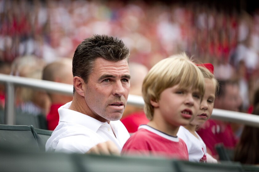 Jim Edmonds sits with his family during a game between the St. Louis Cardinals and the Pittsburgh Pirates in 2012.