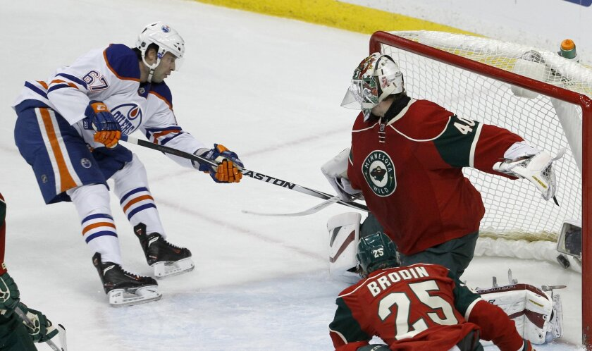 Edmonton Oilers left wing Benoit Pouliot (67) scores on Minnesota Wild goalie Devan Dubnyk (40) as Wild defenseman Jonas Brodin (25) watches during the first period of an NHL hockey game in St. Paul, Minn., Tuesday, Feb. 24, 2015. (AP Photo/Ann Heisenfelt)