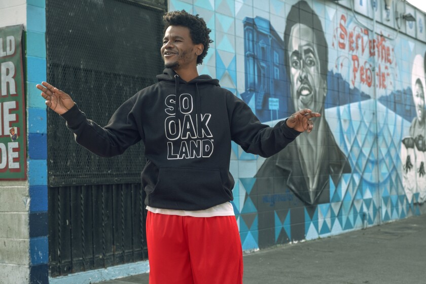 """A man in a """"So Oakland"""" hoodie standing before a mural"""