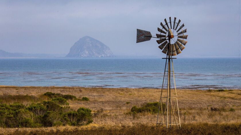 A windmill lines an undeveloped stretch of coast along Cayucos' Estero Bay with Morro Rock visible in the background.