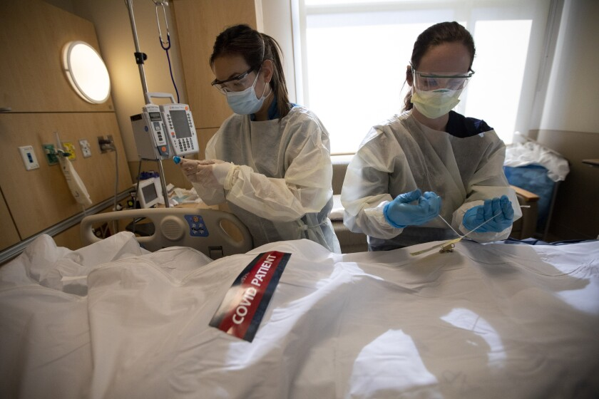 Registered nurses April McFarland, left, and Tiffany Robbins place a body inside a white bag and zip it closed.