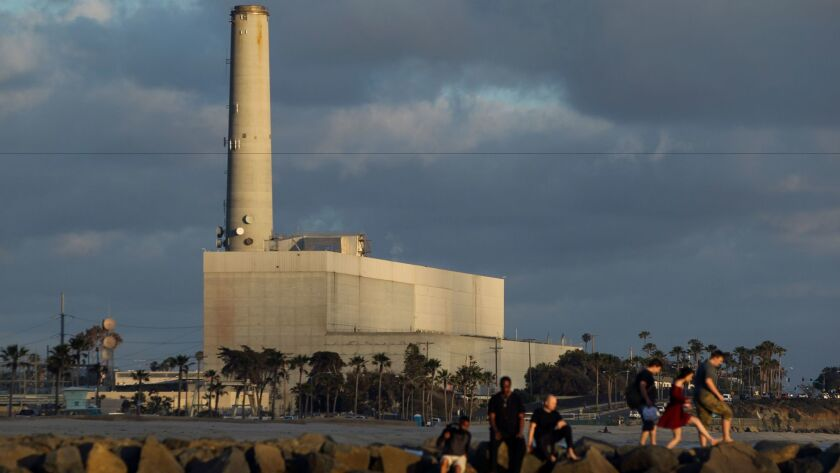People walk along a jetty in front of the Encina Power Station in Carlsbad in a file photo from May 2016. The Encina plant is scheduled to be replaced by the Carlsbad Energy Center.
