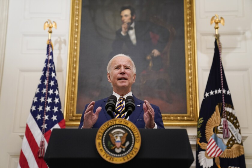 President Biden speaks at a lectern with flags and a painting of Abraham Lincoln behind him.
