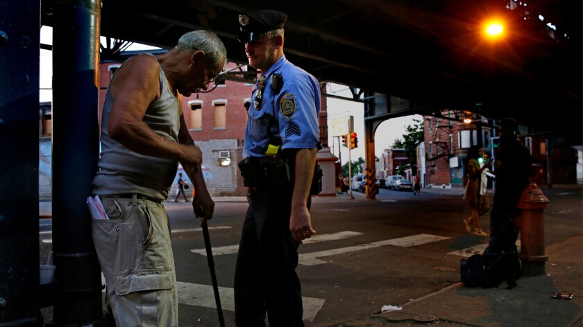 """Dave Parke, a transit police sergeant for the elevated train line that runs through a neglected area of north Philadelphia that cops call """"The Badlands,"""" helps a man trying to get to a bus stop."""