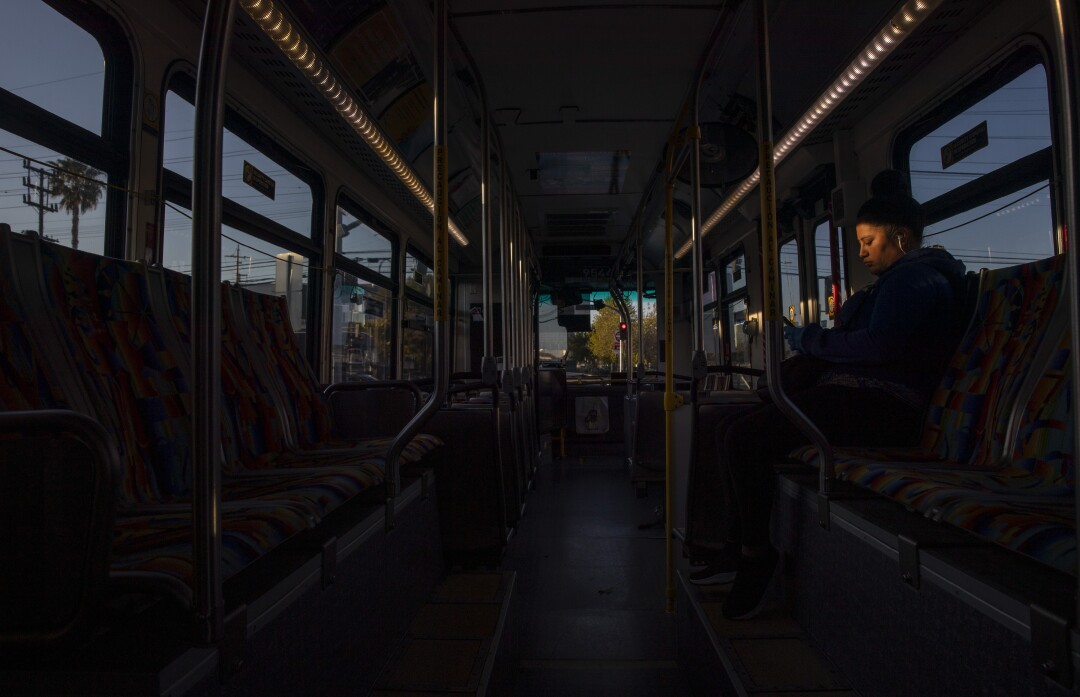 A woman rides an early-morning Orange Line bus in Canoga Park.