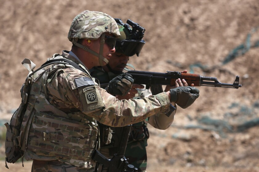 A U.S. Army trainer, left, instructs an Iraqi military recruit at a base in Taji on April 12, 2015.