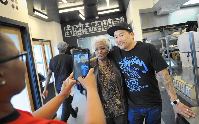 Tabitha O'Neal, left, takes a photo of her mother, Delores, with chef and Locol co-founder Roy Choi