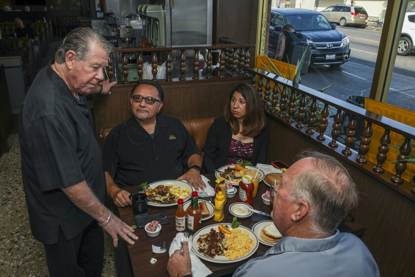 Norm Langer, owner of Langer's Deli, chats with customers eating breakfast at a table.