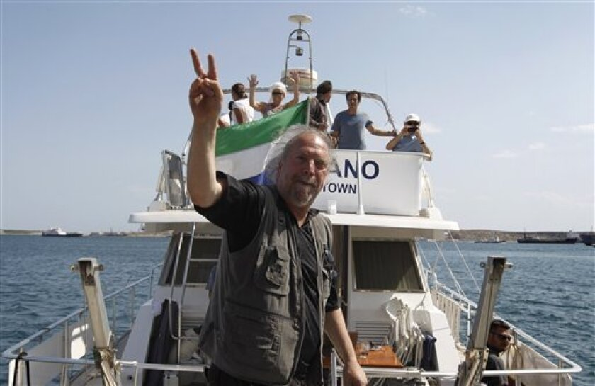 Swedish-Israeli musician and human rights activist Dror Feiler gestures a victory sign onboard a protest ship at the port of Perama, near Athens, Wednesday, July 6, 2011. Organizers of a pro-Palestinian flotilla, planning to challenge Israel's naval blockade of Gaza, have been banned from sailing out of Greek ports. The ship sailed to another harbor outside Athens.(AP Photo/Petros Giannakouris)