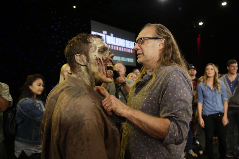 """En esta foto del 8 de junio del 2016, el productor ejecutivo de """"Walking Dead"""" Greg Nicotero, un gurú de los efectos especiales, prepara al actor Joe Giles para una demostración en Universal Studios Hollywood, en Los Angeles. (AP Foto/Jae C. Hong)"""