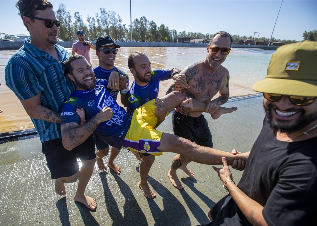Friends carry surfer Adriano de Souza into the water.