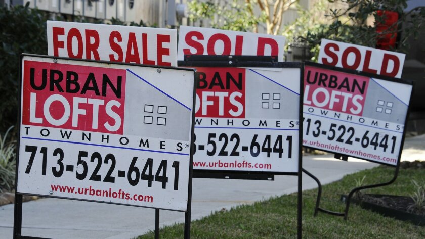 In this Tuesday, Feb. 16, 2016, photo, signs stand outside new townhouses in Houston. On Thursday, March 24, 2016, Freddie Mac reports on the week's average U.S. mortgage rates. (AP Photo/Pat Sullivan)