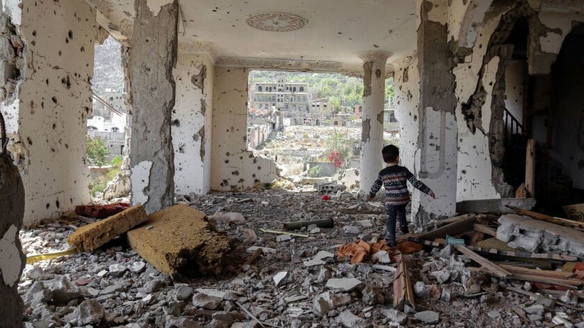 A child walking in the rubble of a building that was destroyed in an air strike in the southern Yemeni city of Taez on March 18.