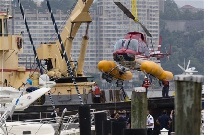 A helicopter is lifted onto a barge at the 79th Street Boat Basin after making an emergency landing over the Hudson river, Sunday, June 30, 2013, in New York. New York authorities say a helicopter carrying four Swedish tourists landed in the Hudson River off Manhattan Sunday, but everyone has been rescued. (AP Photo/John Minchillo)
