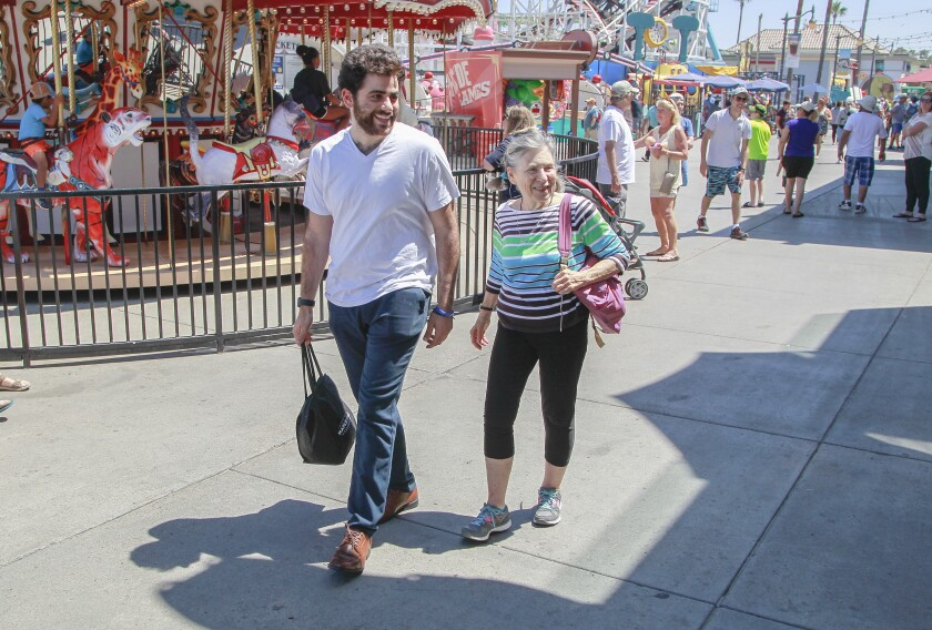 Buddies Golan Corshidi and Joann Baum stroll around Belmont Park in Mission Beach on Aug. 15. The two were matched eight months ago through the Jewish Family Service of San Diego's Friendly Visitor Program.